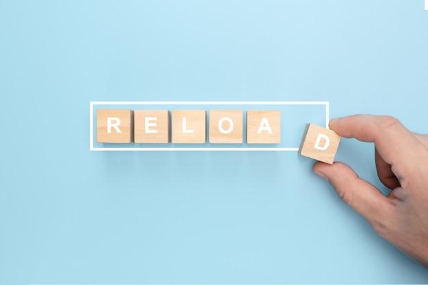 Mão de homem segurando um cubo de madeira com a palavra recarregar sobre fundo azul. Foto Premium