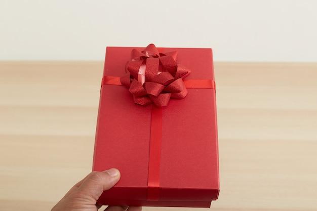 Mão de homem segurando uma caixa de presente vermelha Foto Premium