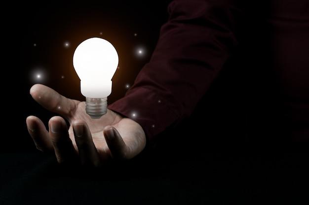 Mão de homem segurando uma lâmpada Foto Premium