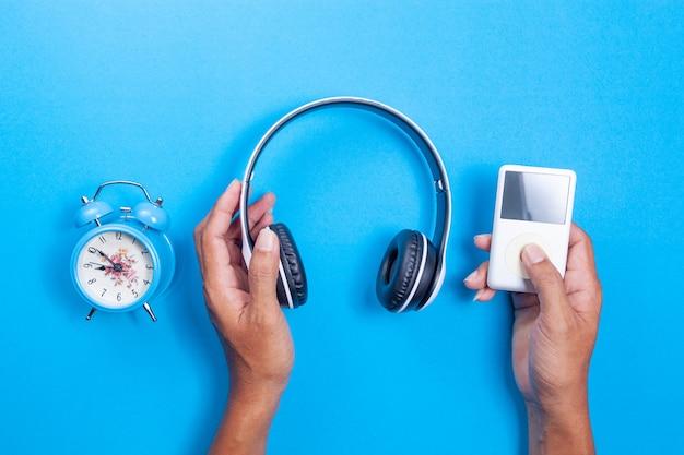 Mão de homem segurar fone de ouvido sem fio, media player, despertador azul sobre fundo de papel azul Foto Premium
