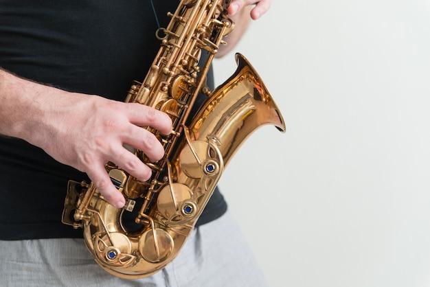 Mão de homem tocando saxofone Foto Premium