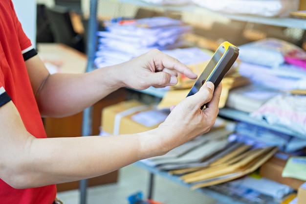 Mão de homem tocando um scanner enquanto estiver usando-o para trabalhar no armazém Foto Premium