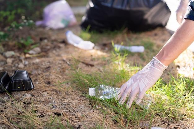 Mão de homem tocar garrafa de plástico no parque ao ar livre Foto Premium