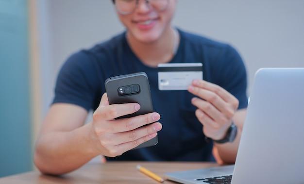 Mão de homem usando telefone celular para pagamento on-line com cartão de crédito Foto Premium