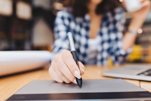 Mão de imagem closeup de mulher projetando na mesa na biblioteca cercam coisas de trabalho. laptop, trabalho criativo, design gráfico, freelancer, estudante inteligente, trabalho de amor. Foto gratuita