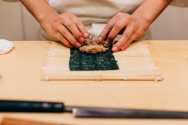 Mão de japonês omakase chef rolando um tuna nori mão rolo ordenadamente por sua mão Foto Premium