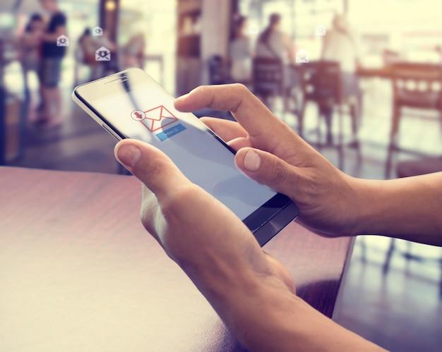 Mão de macho usando telefone celular para abrir nova caixa de entrada de mensagem de email Foto Premium