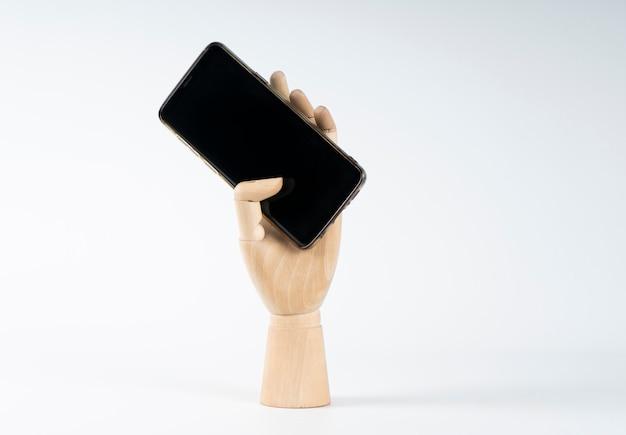 Mão de madeira, agarrando um celular Foto Premium