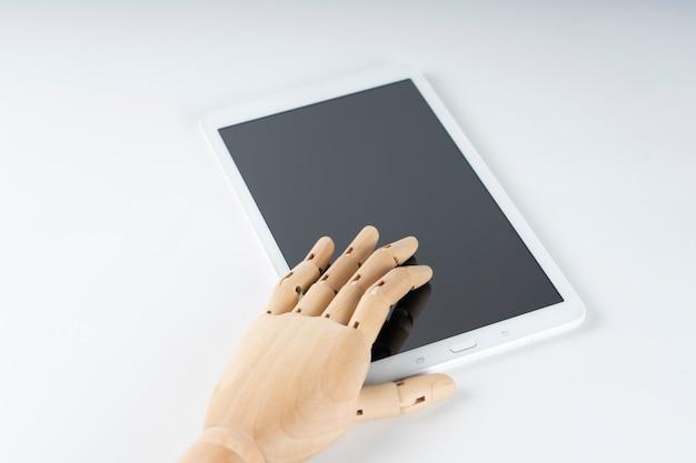 Mão de madeira tocando uma pastilha branca Foto Premium