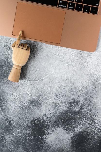 Mão de madeira trabalhando em um laptop. conceito de comunicação e trabalho no escritório. Foto Premium