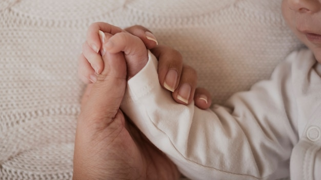 Mão de mãe segurando bebê pequeno braço Foto gratuita