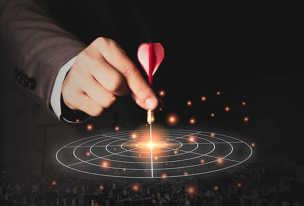 Mão de marketing executivo segurando o dardo vermelho, colocado no centro da placa de destino. objetivo de investimento empresarial e conceito de alvo. Foto Premium