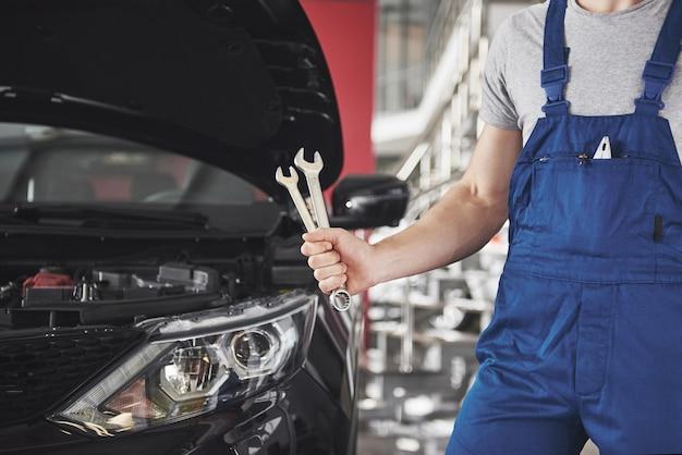 Mão de mecânico de automóveis com uma chave inglesa. oficina de reparação automóvel. Foto gratuita