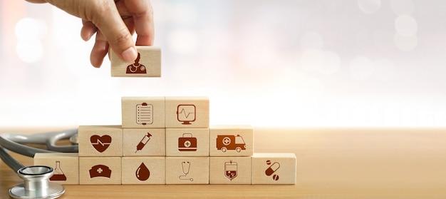 Mão, de, medicina, doutor, segurando, bloco madeira, e, empilhando Foto Premium