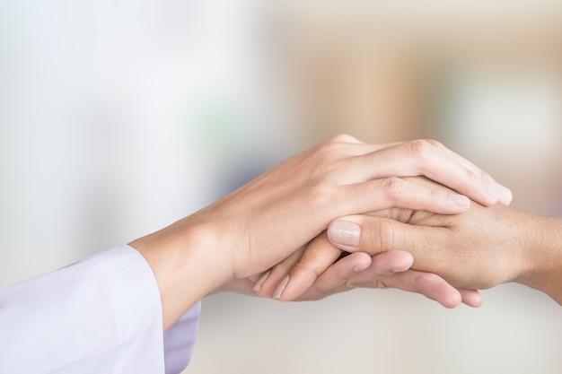 Mão de médico feminino reconfortante paciente com desfoque de fundo do quarto de hospital Foto Premium