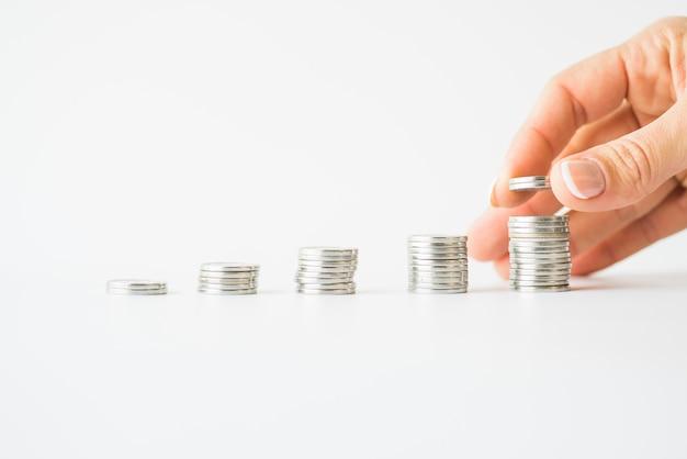 Mão de mulher, adicionando moedas para empilhar Foto Premium