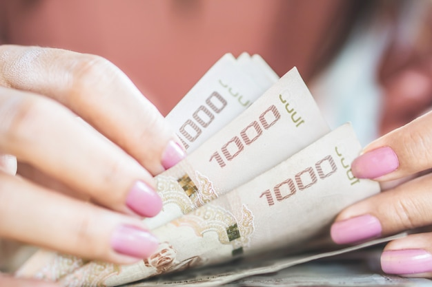Mão de mulher asiática contando dinheiro moeda de papel baht tailandês Foto Premium