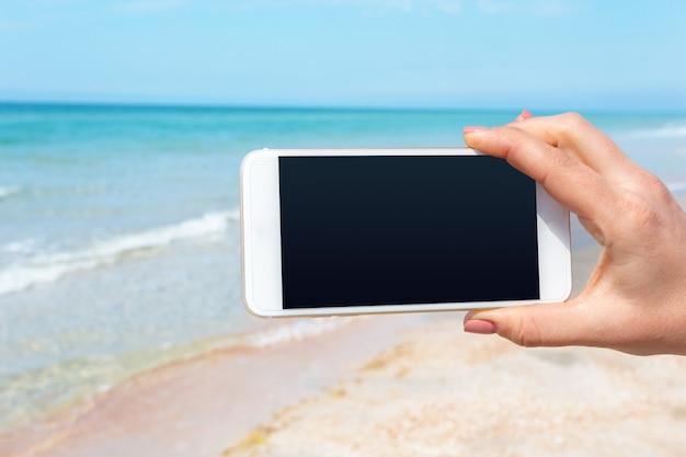 Mão de mulher bonita usando telefone inteligente na praia Foto Premium