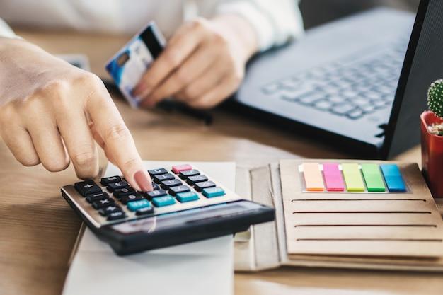 Mão de mulher calcular as despesas de cartões de crédito Foto Premium