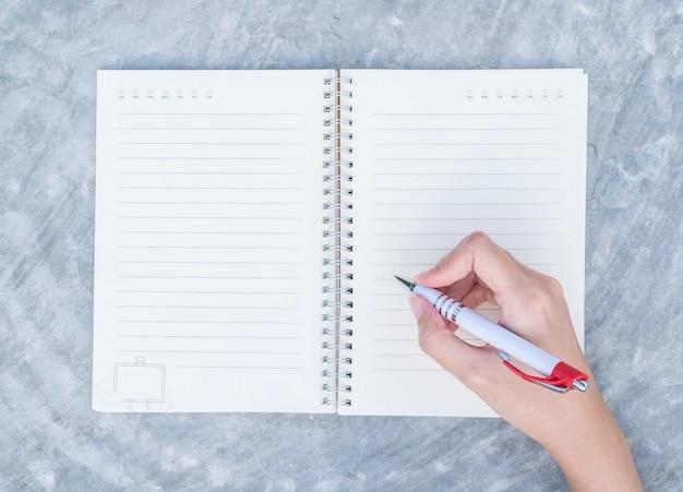 Mão de mulher closeup escrevendo no caderno na mesa de concreto em vista superior texturizado fundo sob luz do dia no jardim Foto Premium