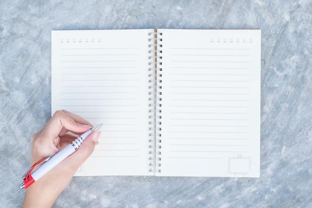 Mão de mulher closeup escrevendo no caderno Foto Premium