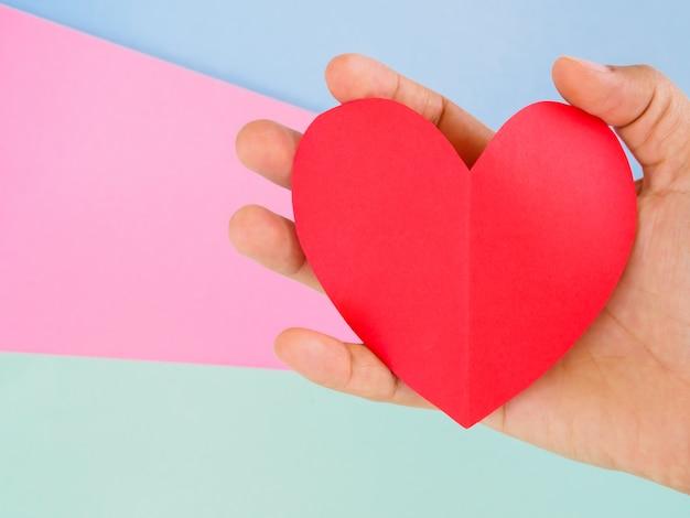 Mão de mulher closeup segurando coração de papel vermelho Foto Premium