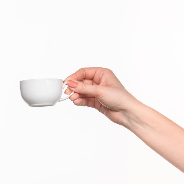 Mão de mulher com copo branco perfeito em fundo branco Foto gratuita