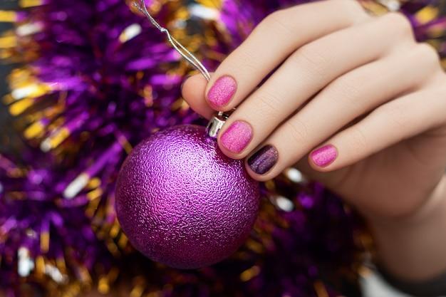 Mão de mulher com design de unhas de natal e ano novo segurar esfera de brinquedo brilhante Foto gratuita