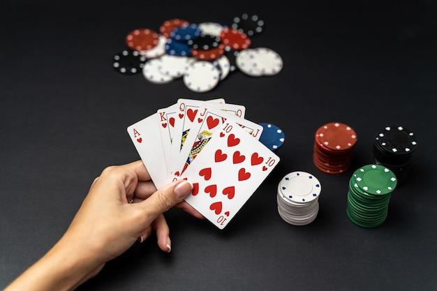 Mão de mulher com mão de royal flush jogando cartas com fichas de poker. conceito de jogo de poker Foto Premium