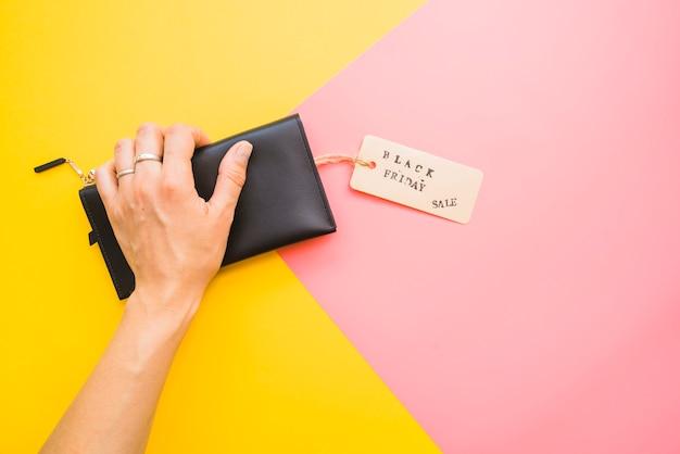 Mão de mulher com saco de embreagem e tag Foto gratuita