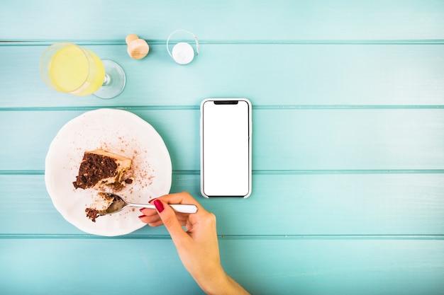 Mão de mulher comendo pastelaria com bebida e celular na mesa Foto gratuita