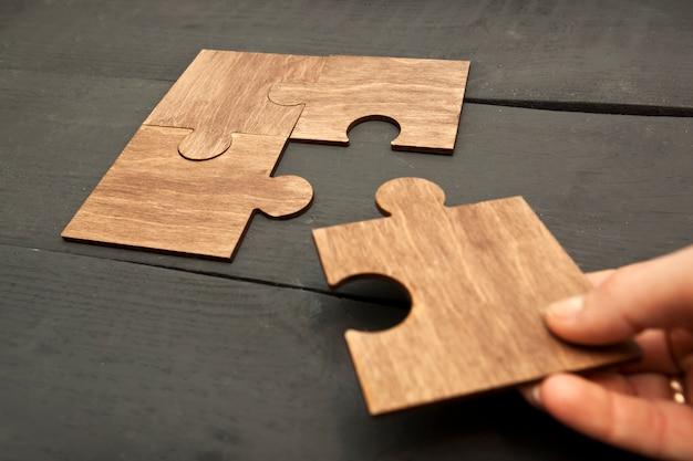 Mão de mulher conectando quebra-cabeças uns aos outros Foto Premium