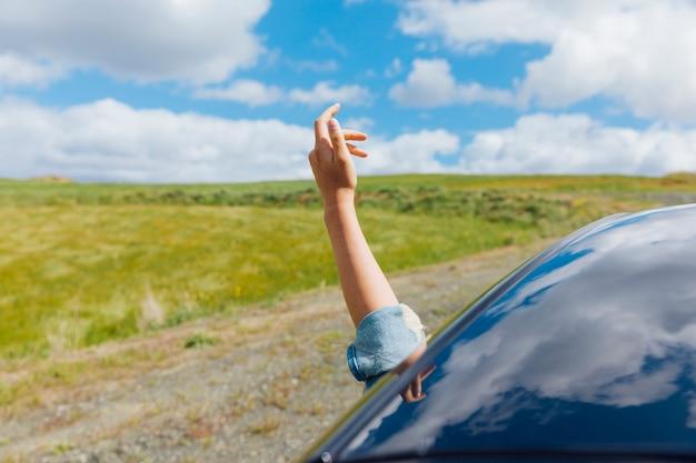 Mão de mulher contra o pano de fundo da natureza Foto gratuita