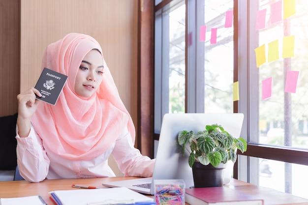 Mão de mulher de negócios muçulmano linda nos segurando passaporte planejando viajar. Foto Premium