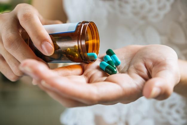 Mão de mulher derrama as pílulas de medicamento fora da garrafa Foto gratuita