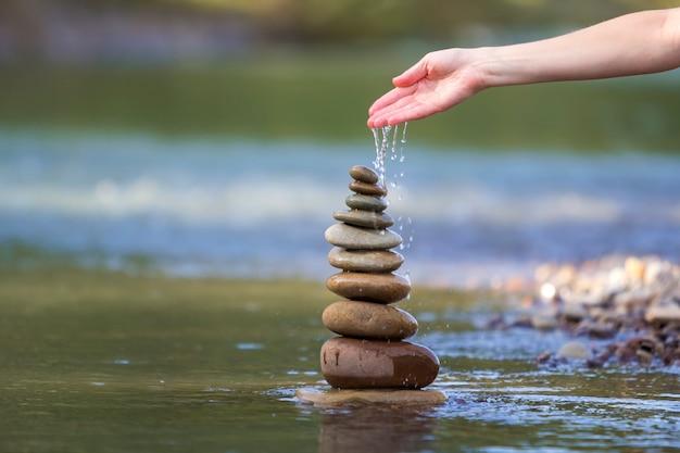 Mão de mulher derramando água nas pedras equilibradas como pirâmide Foto Premium