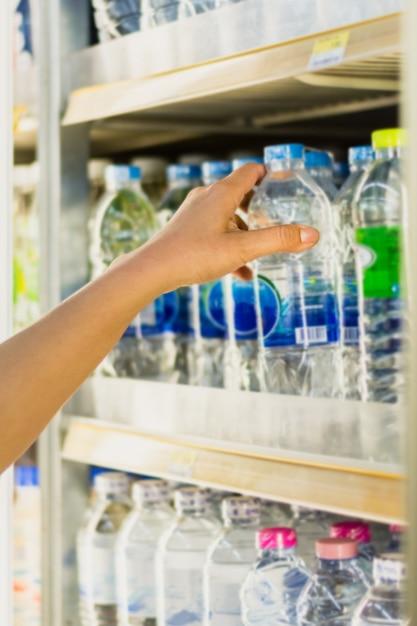 Mão de mulher escolher produto de prateleiras de geladeira de loja de conveniência Foto Premium