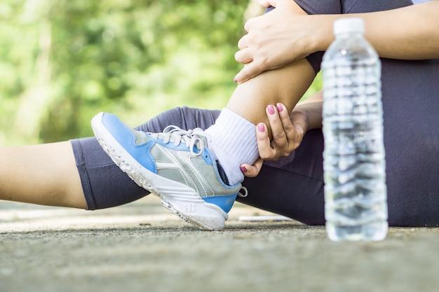 Mão de mulher esporte massageando sua dor nas pernas Foto Premium