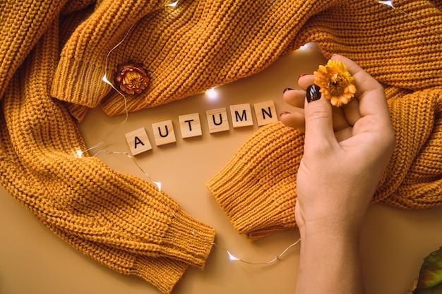 Mão de mulher, folhas de bordo amarelas e flores, guirlanda brilhante em um suéter de malha amarela Foto Premium