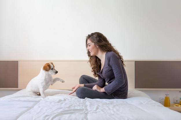 Mão de mulher jovem e bonita cinco com cão pequeno bonito sobre branco Foto Premium