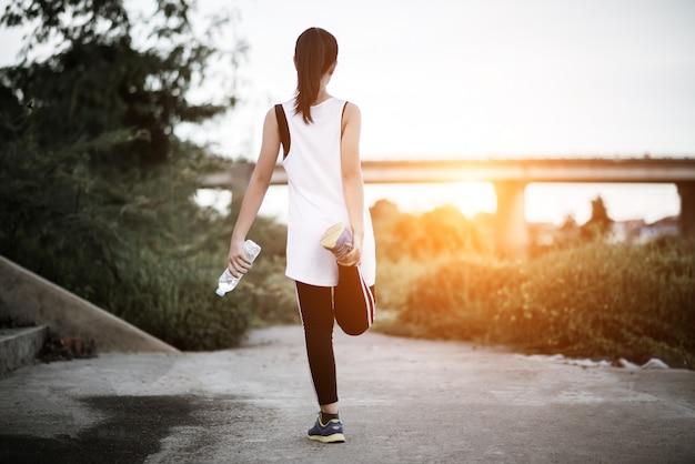 Mão de mulher jovem fitness segurando a garrafa de água após a execução do exercício Foto gratuita