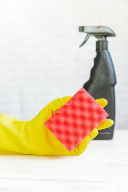 Mão de mulher na luva de borracha amarela, segurando a esponja de limpeza. . produto de limpeza. Foto Premium