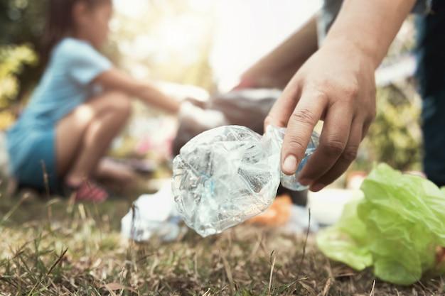 Mão de mulher pegando a garrafa de lixo para limpeza no parque Foto Premium