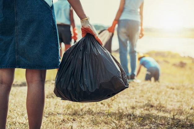 Mão de mulher pegando lixo e mão segurando o saco preto no parque Foto Premium