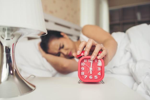 Mão de mulher preguiçoso segurando o despertador na cama Foto gratuita