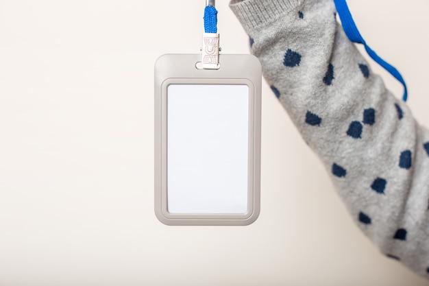 Mão de mulher segura crachá, crachá, identificador de crachá, cordão na parede de luz Foto Premium