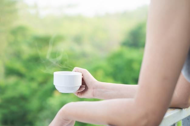 Mão de mulher segurando a xícara de café quente bebendo ao ar livre Foto Premium