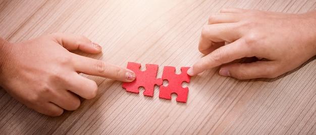 Mão de mulher segurando as peças do quebra-cabeça no escritório Foto Premium