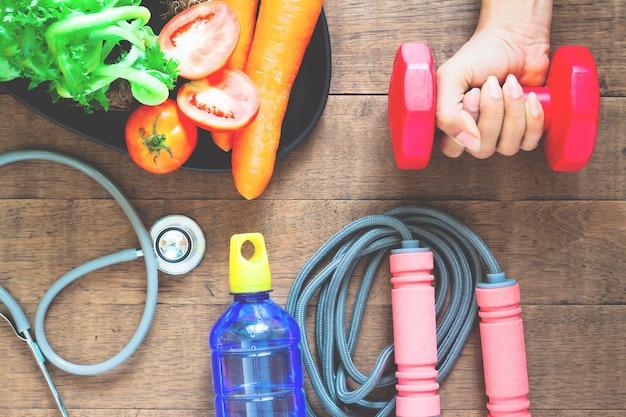 Mão de mulher segurando halteres, alimentos saudáveis e equipamentos de fitness em madeira Foto Premium