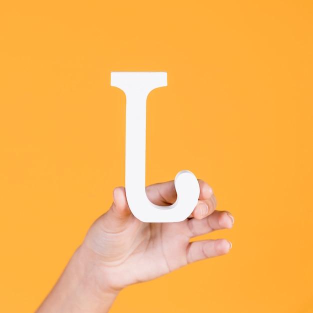 Mão de mulher segurando o alfabeto branco j Foto gratuita
